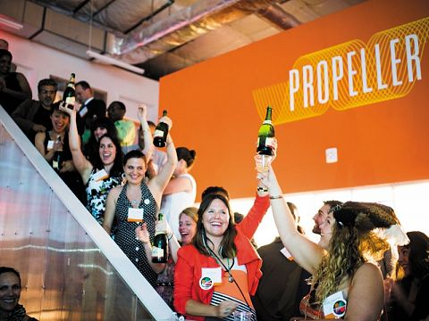 The graduating class of Accelerator Fellows pops the champagne, in completion of Propeller's 10-month Social Venture Accelerator.